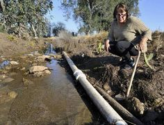 Seville native Rebecca Quintana shows a water line that provides part of Seville with household water from the town's nearby pump. The plastic pipe replaced a rusty pipe that Quintana says may have dated back to the early 1900s. Both pipes are in an irrigation ditch with standing, fetid water. Quintana wonders if the water had anything to do with the May 2015 death of her daughter Regina Lujan. Breast cancer caused Lujan's death.