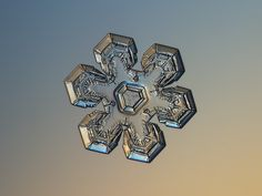 Snowflake macro photo: Massive gold - real snow crystal with relief and glossy surface, sparkling on bright orange-blue gradient background. Available in two color variants (with warm golden and cold silver light) as free downloads, prints, full HD 1080p wallpaper and licenses for commercial use.