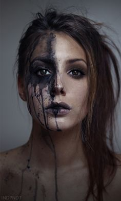 reflection is envisioned as one half of the woman's face is clear and the other is splattered with paint.