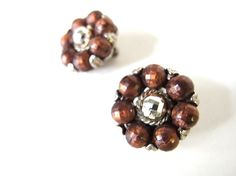 This elegant set of vintage 1950s faceted brown / bronze and silver cluster clip on earrings has bronze faceted beads strung together with cording, then