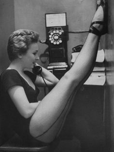 Photographer: Gordon Parks Dancer Mary Ellen Terry Talking with Her Legs Up in Telephone Booth, 1952