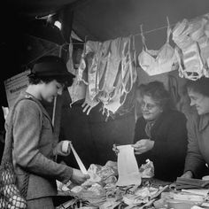 Nina Leen - Description A woman selling bras, girdles and other articles at the open air stalls - 1950
