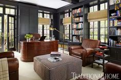 Handsome, masculine black paint covers the walls in this study, but it's the houndstooth hair-on-hide ottoman that really steals the show. - Traditional Home ® / Photo: Werner Straube / Design: Suzanne Kipp