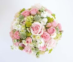 White, pink and green. Compact and round wedding bouquet.