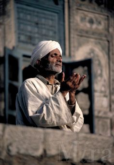 Turbaned man praying at the mosque in Srinagar, Kashmir. Muslim prayers are required to be said five times a day, facing Mecca.