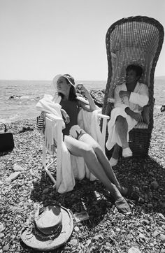 "The actress Audrey Hepburn photographed with the actor Albert Finney by Terry O'Neill in St. Tropez (France), during a break in the filming of ""Two for the Road"", in June 1966.  Audrey was wearing: Swimsuit: Ken Scott (red, created specially for the wardrobe of her character Joanna Wallace). Hat: Foale and Tuffin (of twill cotton, of the collection for the Spring/Summer of 1966)."