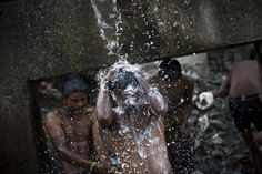New Delhi, India Indian men bathe in water from a broken pipe next to a sewage canal on a cold morning.