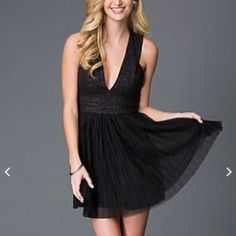 NWT little black dress Fun and flirty black dress with deep v neck and flowy skirt area. X in the back and a hidden back zipper. Size 7 Dresses Mini