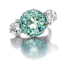 An aquamarine and diamond three-stone ring centering a circular-shaped aquamarine, weighing 14.01 carats, flanked by round brilliant-cut diamonds, weighing 1.43 and 1.38 carats; mounted in 14k white gold; size 7 3/4