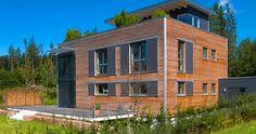 Bauhaus Modern Living mit Holzfassade und Flachdach von Baufritz