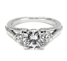 """Tacori's modern take on the three-stone ring features a round brilliant-cut center stone, accented with two round side stones sitting within an unexpected and unique split diamond-accented band. Signature crescents mark the ring as """"Tacori."""""""