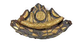 """A sword pommel from the Bedale Hoard. Archaeologists have revealed hacked-off silver ingots engraved with the symbol of the cross and a large sword pommel featuring animal and gold leaf decorations by """"highly skilled"""" Anglo-Saxon craftsmen on one of the most important hoards found in the north of England."""