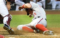 Painful run - Ryan Zimmerman of the Washington Nationals slides safely into home plate as the throw hits him in the face during the second inning of a game against the Arizona Diamondbacks on May 11 at Chase Field in Phoenix. - © Norm Hall/Getty Images