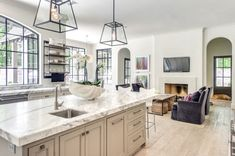 The light and bright kitchen, awash in whites and muted grays, is inviting to the entire downstairs with open archways leading to adjacent spaces.