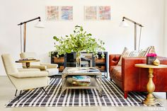 Lounge area in office with white walls, brown leather couch, large plants, colorful artwork, silver coffee table, black and white checkered rug, white chair, floor lamps, and gold coffee table