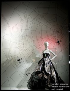 The two things that I like about this display are that the mannequin interacts with the web and the giant spider shadow in the background created with string art. Bergdorf Goodman window display
