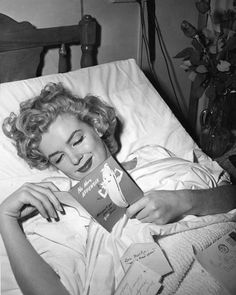 A recuperating Marilyn Monroe reading a get-well card.