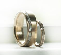 You and your spouse deserve a matching set as unique as your love. This set   features a 10k gold ring with an offset mother of pearl inlay and a 10k   gold stacking band with a mother of pearl inlay. Additional wood &inlay   options available upon request.    Available in: TITANIUM, SILVER, BL