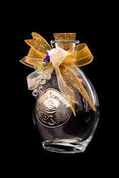 Handmade First Communion party favors used for storing holy water that are made out of a glass bottle decorated with gold ribbon and a label with a chalice and host.