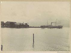Anonymous | Gezicht op een baai met een schip en gebouwen op Ambon, Anonymous, c. 1900 - c. 1920 | Onderdeel van Reisalbum met foto's van Ambon.