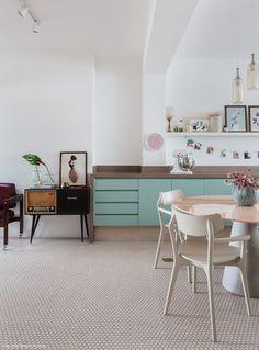 Sala de jantar tem mesa com base de concreto e tampo laqueado na cor rosa. Ao lado, bancada de concreto e marcenaria na cor verde menta.