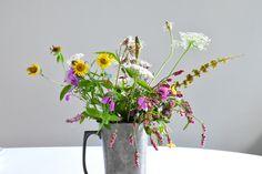 Ramillete de flores silvestres en jarra de cerveza de latón