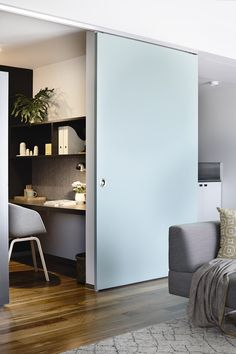 Sliding blue door opens to home office and grey desk chair