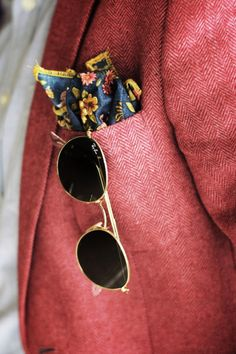 Coral colored tweed jacket, floral cotton pocket square, and Ray Ban shades