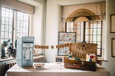 Grey postbox and vintage suitcase for cards with Kraft paper bunting sign - Image by Kerry Diamond Photography - Bride wears Bespoke Gown & Veil by Dana Bolton. Outdoor Ceremony at Voewood House in Norfolk with Picnic Wedding Breakfast & Lawn Games.