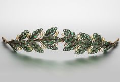 An emerald, pearl and diamond tiara, circa 1900  Designed as a laurel wreath, pierced and millegrain-set with circular, step and mixed-cut emeralds, interspersed with pearl 'berries' and rose-cut diamond stems, pearls untested for natural origin. Click to enlarge: http://assets5.pinimg.com/upload/137641332332699120_Pr4Zfsxp.jpg