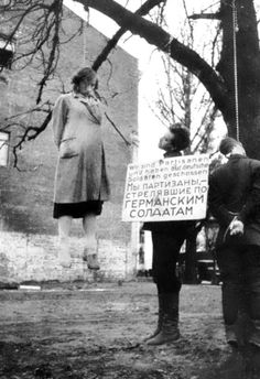 """Three Soviet citizens are hanged from a tree by German forces with a placard reading, """"We are partisans and have shot at German soldiers"""" in both German and Russian. Near Minsk, Belarus. 1942."""