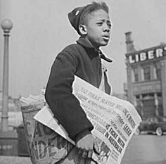 Newspaper boy handing out the Chicago Defender.