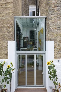 A double height frameless glass infill extension with aluminium bifold doors and glass beams.