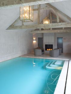 Indoor Pool with seating area and fireplace.