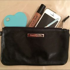 """Black Tiffany and Co. pouch/wristlet  100% authentic, black metallic leather Tofdany and Co. pouch! 5"""" x 8.75"""". Beautiful supple leather; iconic Tiffany blue leather interior  holds SO much! Came in the reversible totes that Tiffanys made a few years ago but I have 2, so 1 needs a loving home  has a loop on the end where it used to be attachable to the purse, but is perfect for a wristlet strap or other charm strap!  Any questions, please ask! Tiffany & Co. Bags Clutches & Wristlets"""