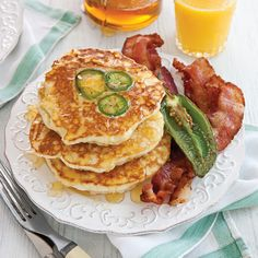 Drenched in honey, these cheesy cornmeal flapjacks make a filling supper when paired with a generous helping of skillet-crisp bacon.