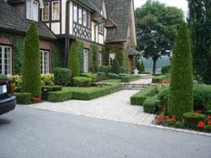 A formal front yard design that is very well manicured. This front walkway is wide and receptive to traffic entering the walkway, and narrows as it takes the user to the front door.  Picture compliments of www.ogslandscape.ca