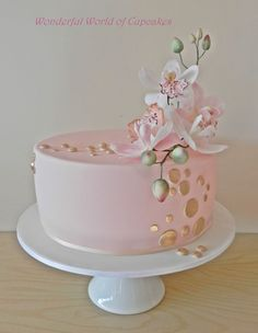 """10"""" Chocolate cake with sugar paste Cymbidium Orchids and fondant gold buttons. Flower stems are enclosed into a flower pick which is t..."""
