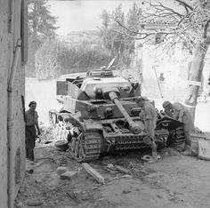 Troops examining the wreck of a German PzKpfw IV tank knocked out in the village of San Savino, 19 September 1944.