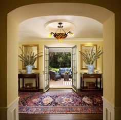 What a statement - gorgeous rug, wood floor, fantastic tables & arrangements, arch and to top is all off, French doors to the patio. Beautifully done.