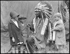 "Young Chief ""Little Wound"" Age 57 - Sioux Indian from Pine Ridge, South Dakota, telling youngsters story, 1928 (photo by Leslie Jones)"
