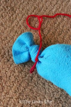 I tied a length of wool to the top of the sock cat toy so that I can pull it around for the cats to chase!
