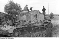 """A Panzer IV of the 3rd Panzer Division, nicknamed """"Grizzly Bear"""", and its crew take a break on an unpaved road in Russia, August 1943."""