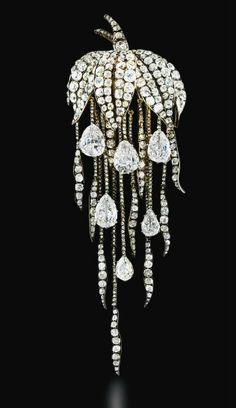 1860 diamond brooch: pavé-set old-cut diamond leaf canopy suspending a graduated fringe of diamond trails with six pear-shaped diamond drops, mounted in silver and gold, diamond drops.