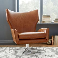 Love the idea of a modern arm chair in library, paired with a slightly more traditional shaped sofa. Hemming Leather Swivel Armchair | west elm