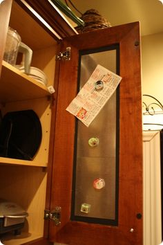 Hot glue galvanized metal sheets on inside of cupboard...hides all the junk usually on the fridge!