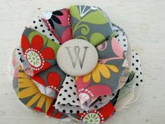 Duh...make the felt flower with regular fabric, and throw an initial on the covered button!  Cute personalized hair clip!