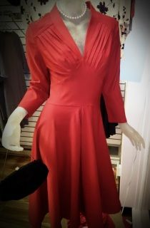"""Beautiful vintage inspired cherry red dress. Featuring pleated bust, long sleeves, stretch fabric, and side zipper. This figure flattering dress is reminiscent of the 1950's. Measures 38-40"""" bust, 30-32"""" waist, free hip, 45"""" length. New with tags. 60% Rayon, 30% Cotton, 5% spandex. Hand wash, hang dry or dry clean."""