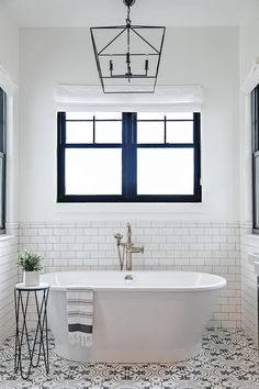 Luxurious black and white bathroom boasts a black and white accordion style accent table placed on black and white cement quatrefoil tiles beside an oval freestanding bathtub finished with a satin nickel vintage floor mount tub filler.