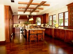 Warm cherry wood used extensively in this U-shaped kitchen, throughout flooring, cabinetry, and island, plus central exposed cross beams.